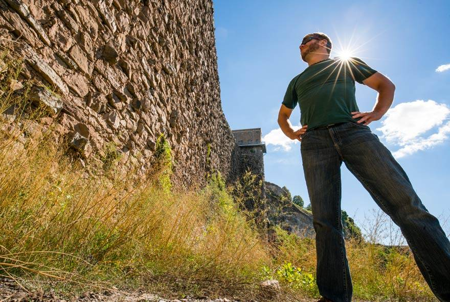 A man standing on grass in Niagara Falls State Park looks up at the Schoellkopf site