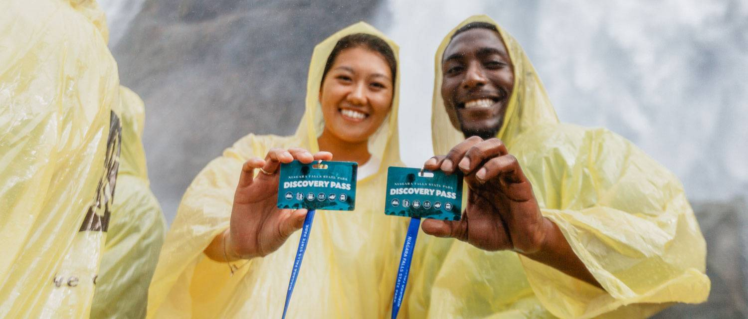 Two people wearing ponchos holding Discovery Pass cards