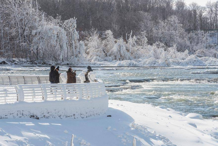 Tourists overlooking rapids in Niagara Falls State Park in winter in New York