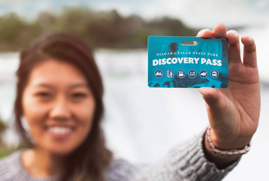 girl holding up a Discovery Pass card with Niagara Falls in the background