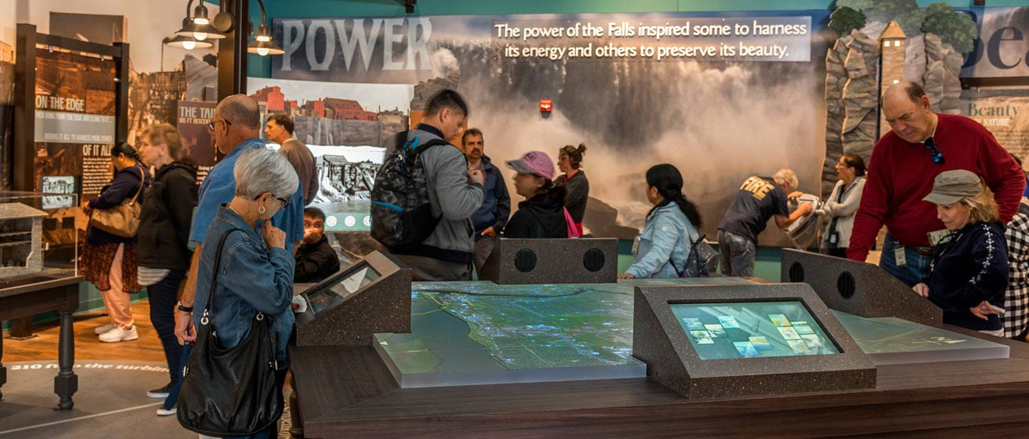 Niagara Falls State Park visitors look at an exhibit inside the World Changed Here Pavilion