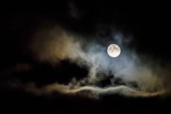A full moon at night is surrounded by clouds