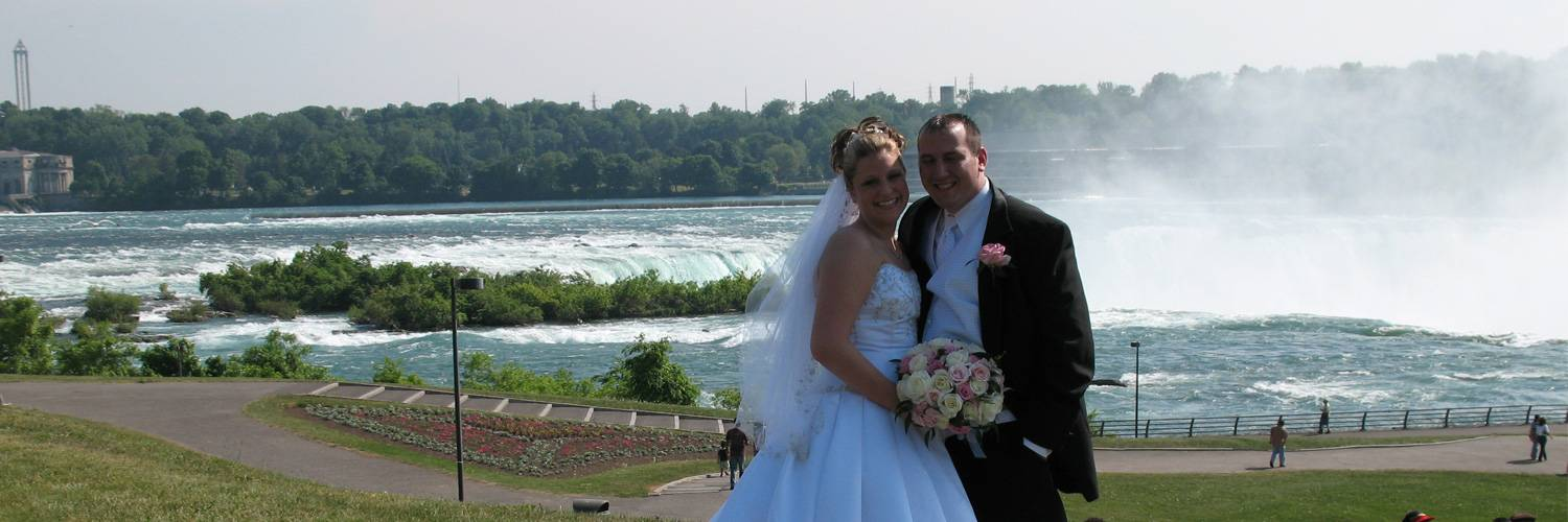 newly married couple in front of niagara falls